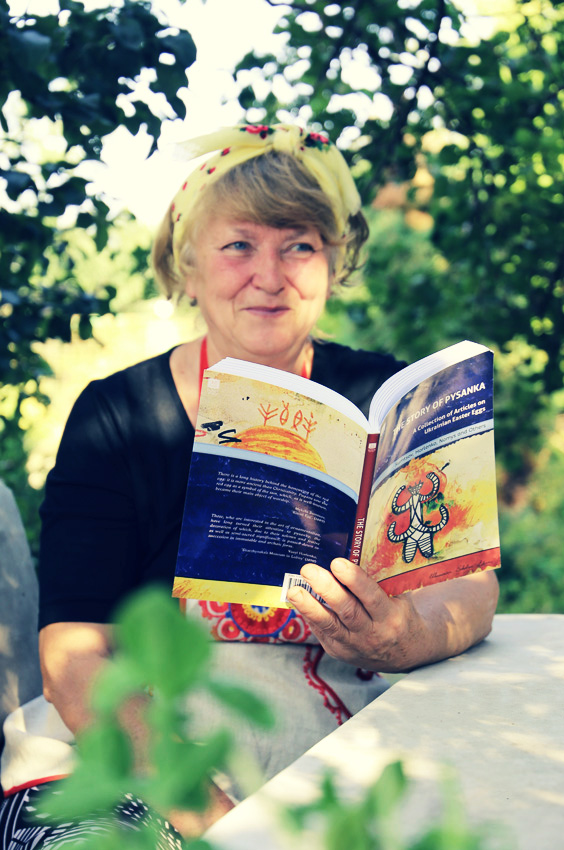 """Woman wearing a kerchief sits in a garden and holds """"The Story of Pysanka"""" book"""