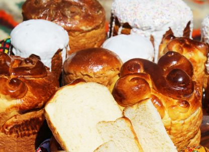 Several paskas, Ukrainian Easter bread, with symbolic dough ornaments and white glaze.